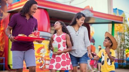 Una familia joven de 4personas sonríe mientras el padre sostiene una bandeja con comidas y bebidas