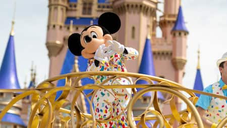 Mickey forms a heart shape with his hands as he passes by Cinderella Castle on a parade float