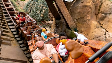 Un père et son fils font un tour à bord de Seven Dwarf's Mine Train de Disney en respectant la distanciation physique