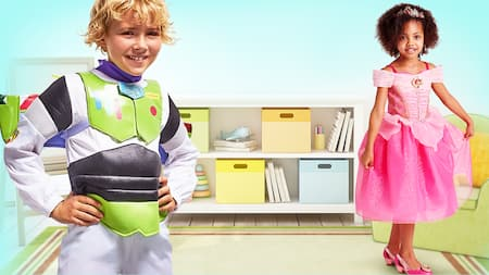 Um menino usa uma fantasia de Buzz Lightyear e uma menina com uma fantasia da Princesa Aurora