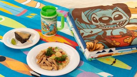 Un dîner, un dessert et une boisson dans un thermos sur une serviette de plage, à côté d'une pile de serviettes pliées