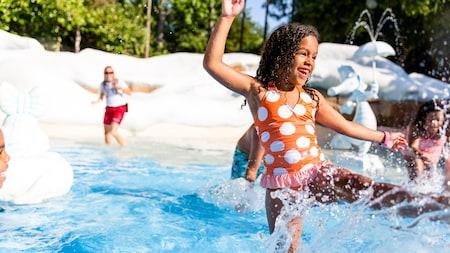 Menina se diverte na água enquanto outras crianças brincam ao redor