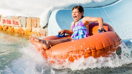 A little girl slides down into the water on an innertube