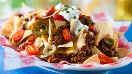A plate of nachos topped with chili, jalapenos, tomatoes, sour cream and chives
