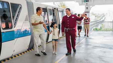 Des visiteurs sortent du monorail alors qu'ils sont dirigés par un membre de l'équipe Disney