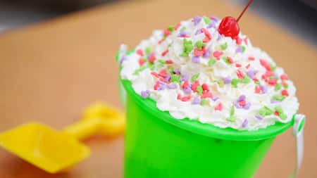 A bucket of ice cream topped with whipped cream, sprinkles and a cherry