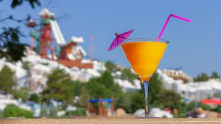 A cocktail with a straw and umbrella on a table in front of a snowy mountain with a waterslide