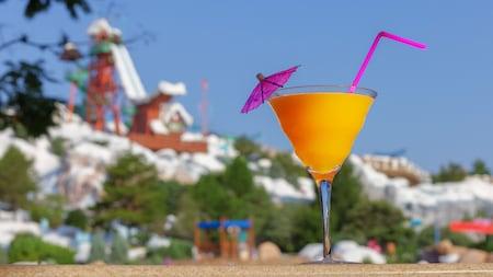Un cocktail avec une paille et un parasol sur une table devant une montagne enneigée avec une glissade d'eau
