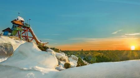 Una montaña nevada frente a árboles con un tobogán de agua en la parte superior