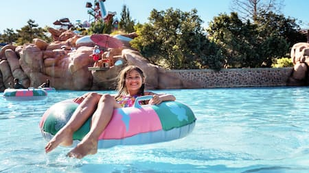 A smiling young girl sits in an inner tube in Melt-Away Bay in Disney's Blizzard Beach