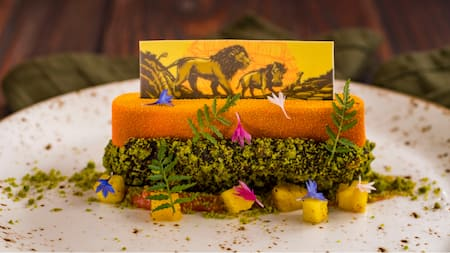 Food arranged on a plate with a small drawing of Simba, Pumbaa and Timon from The Lion King