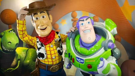 Sheriff Woody tips his hat and smiles with Buzz Lightyear and Rex the Dinosaur.