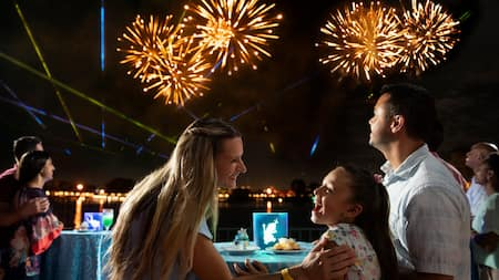 A family watches fireworks while eating dessert