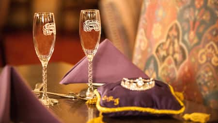 2 champagne flutes next to a tiara on a satin pillow