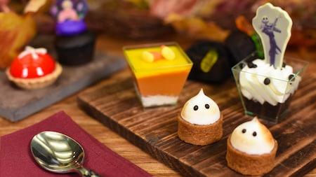 Plusieurs planches de bois sur lesquelles sont posés de petits desserts au thème de l'Halloween sur une cuillère reposant sur une serviette de table