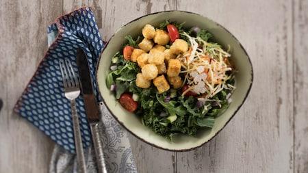 Tigela de tofu frito crocante com especiarias e pimenta-malagueta, com uma salada de legumes crocantes, bolinhas de tapioca e molho