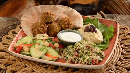 Um prato quadrado com ingredientes para preparar um falafel, incluindo legumes e homus