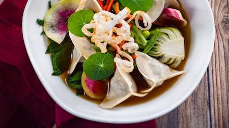 Guiozas de carne vegetariana, servidos com acelga chinesa, vagem comprida chinesa, pimentão vermelho e rabanete em um caldo aromático asiático delicioso.