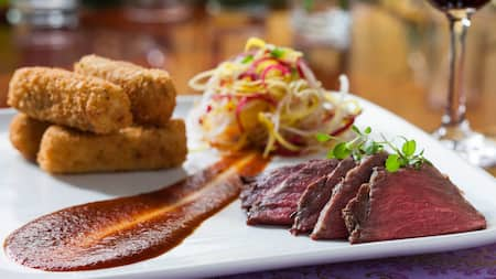 A plate of sliced beef with a side of croquettes