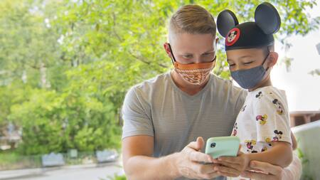 A Dad and his son who's got mouse ears on, both wearing facemasks, look at a cell phone