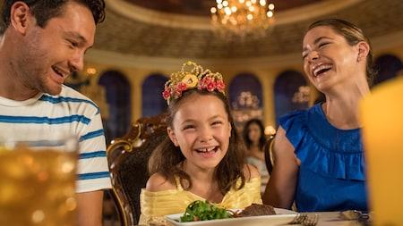 Una niña vestida como Belle come con sus padres en Be Our Guest Restaurant