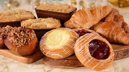 An assortment of breakfast pastries, including muffins, croissants, Danishes and sweet breads