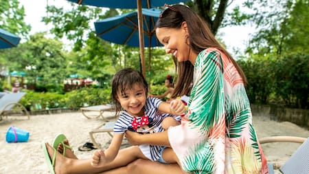 A mother and daughter sit under an umbrella in a lounge chair on a beach