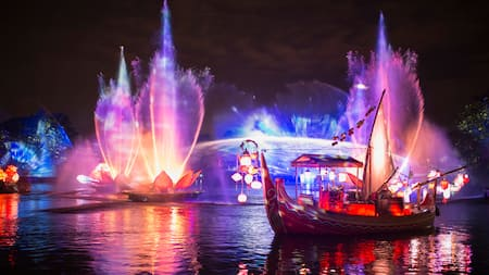 A boat floating past colorful fountains