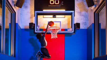 A male Guest demonstrates a slam dunk
