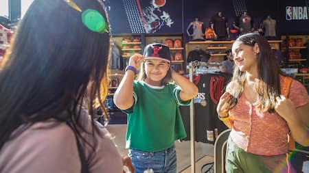 A young female Guest tries on a cap in front of 2 female friends inside the NBA Store