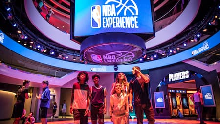 A family of five explore the dramatically lit NBA Experience venue