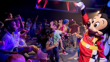Mickey Mouse, vestido con un traje de carrera de autos, baila con niños en una pista de baile