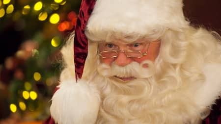 Santa Claus wearing gold framed reading glasses