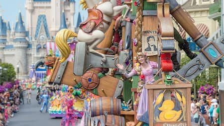 A parade in front of Cinderella Castle featuring Rapunzel on a float shaped like a boat and more characters following behind her
