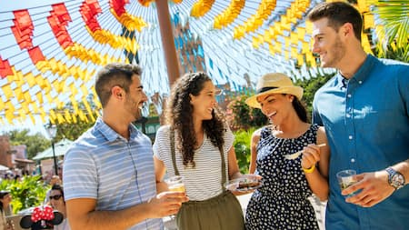 Un grupo de personas sonrientes al aire libre sosteniendo bebidas y comida