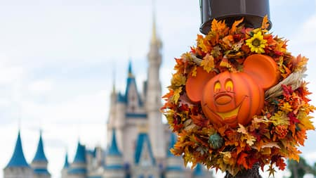 A Mickey Mouse pumpkin head wreath featuring leaves and floral accents attached to a lamppost