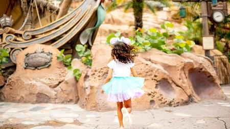 Une jeune fille court vers l'entrée de Under the Sea Journey of The Little Mermaid