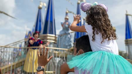 A daughter waves to Snow White and Cinderella while sitting on her father's shoulders