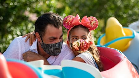 A father and daughter wearing face coverings enjoy riding on Dumbo the Flying Elephant