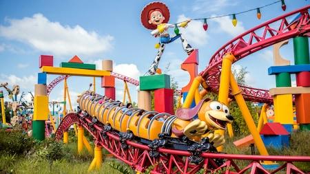 Personas en la atracción Slinky Dog Dash pasando junto a una estatua gigante de Jessie, la vaquera