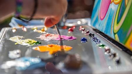 Um pintor mergulhando um pincel na tinta colorida ao lado de uma tela
