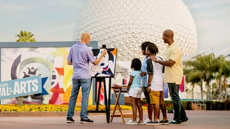 A family watches as an artist puts finishing touches on a portrait of Mickey Mouse at Epcot