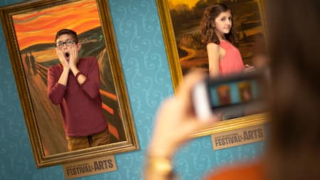 Kids seem to blend in with art as they pose for pictures in front of the backdrops of famous paintings
