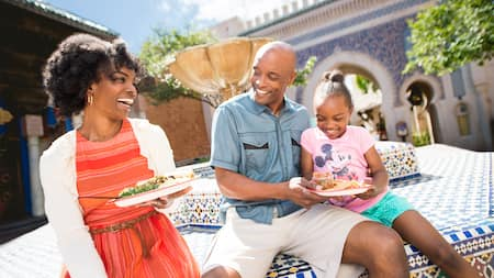 A young family of 3 smiles while sitting on the edge of a courtyard fountain with plates of Moroccan food