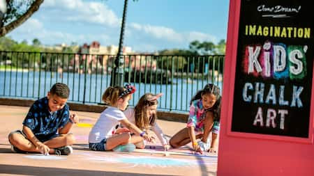 A group of kids sit on the ground drawing with chalk near a sign that reads 'Imagination Kids' Chalk Art'