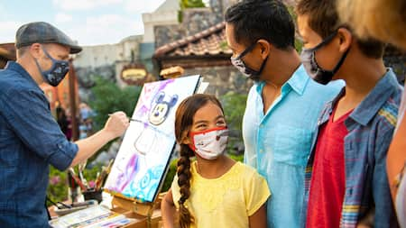 A little girl and her family watching an artist paint a picture