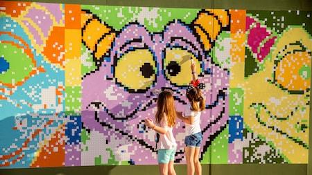 Duas meninas pintando um mural divertido com números do Figment, da Disney