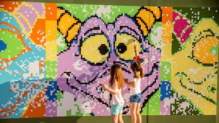 Two girls enjoy a paint by number mural featuring Disney's Figment