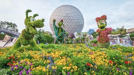 Un jardín de arbustos artísticos en Epcot con Pluto, Daisy Duck y Goofy como jardineros