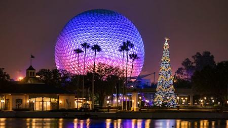 Por la noche, un árbol de Navidad decorado, cerca de palmeras y el icónico símbolo de Epcot, Spaceship Earth